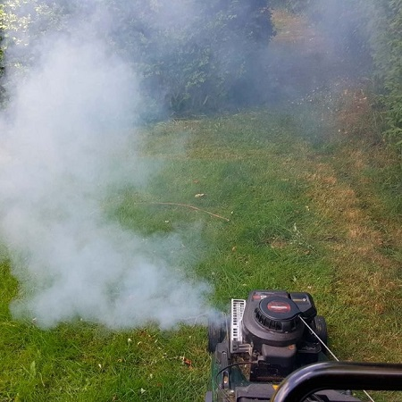 A lawn mower emits black colored smoke in lawn
