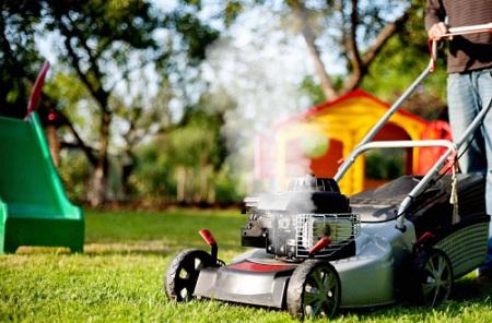 A man operating lawnmower which emits white smoke.