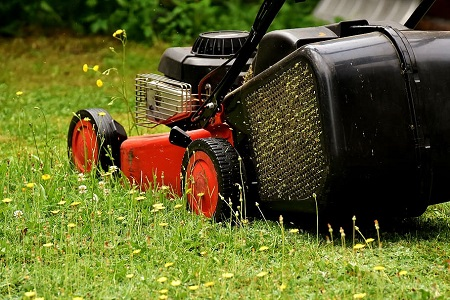 A red color lawn mower mowing the yard