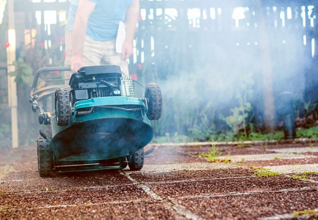 Man facing an issue of black smoke while mowing lawn with lawnmower