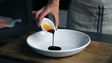 A cup of vinegar poured into a plate